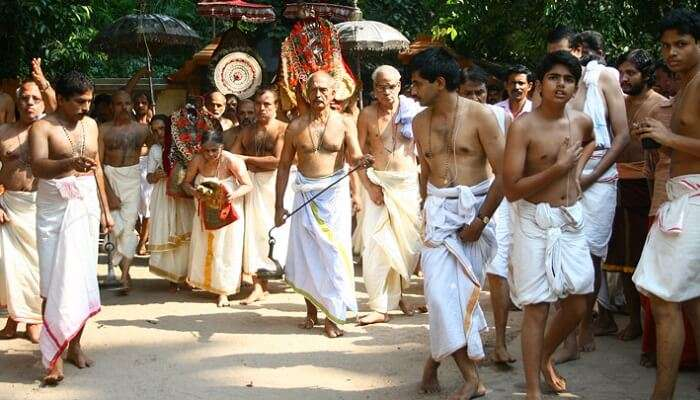 Locals and priests walk during a procession during the Mannarasala Ayilyam festival