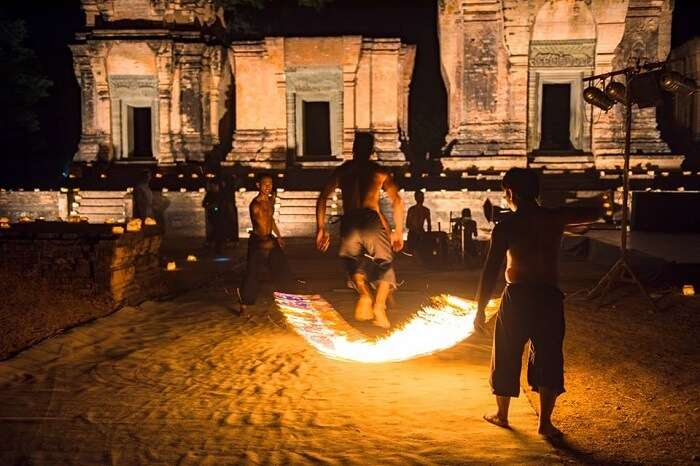 Artists of the Phare Cambodian Circus performing in pront of one of the old temple buildings at night