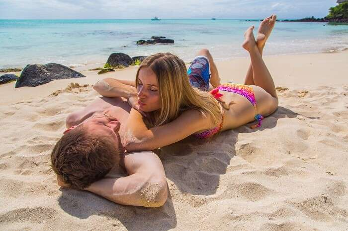 Romantic couple lying on the beach on the beautiful island of Reunion