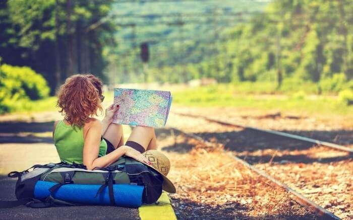 A female traveler reading a map beside rail tracks