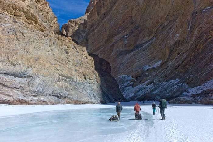 Travelers walking the frozen lake while walking the Chadar trek