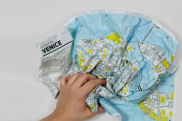 A crumbled waterproof map in a man's hand
