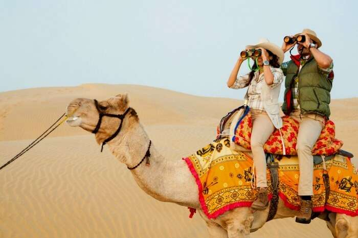 People exploring the vast dunes of desert while enjoying camel safari in Jaisalmer