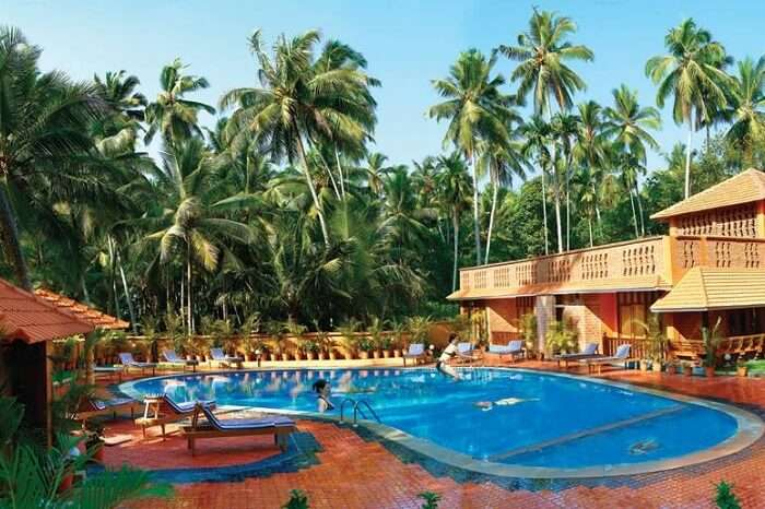 Tourists relaxing at the swimming pool of the Beach and Lake Resort in Kerala