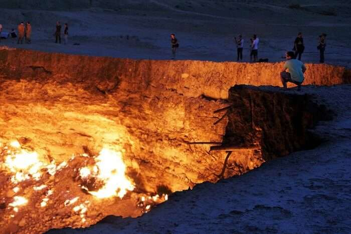 A man sitting on the edge of the Door to Hell in Turkmenistan