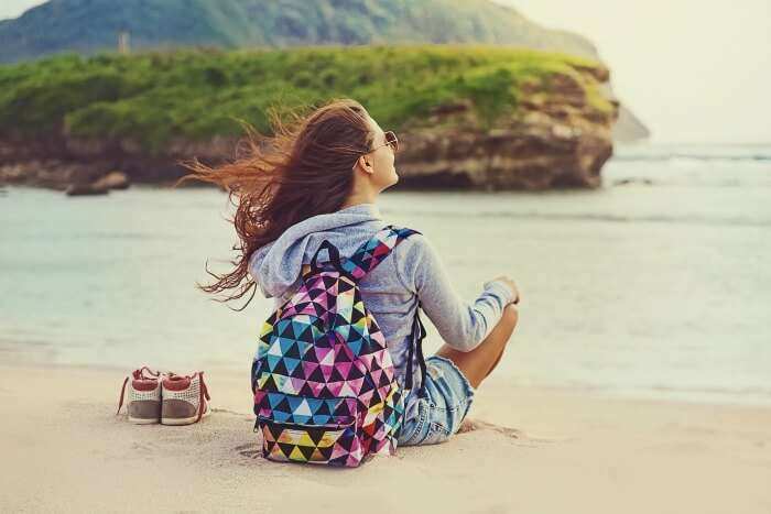 a girl sitting on a beach, free and independent