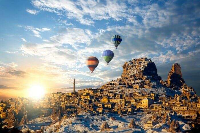 Hot air balloons sailing above the ruins and caves of Cappadocia