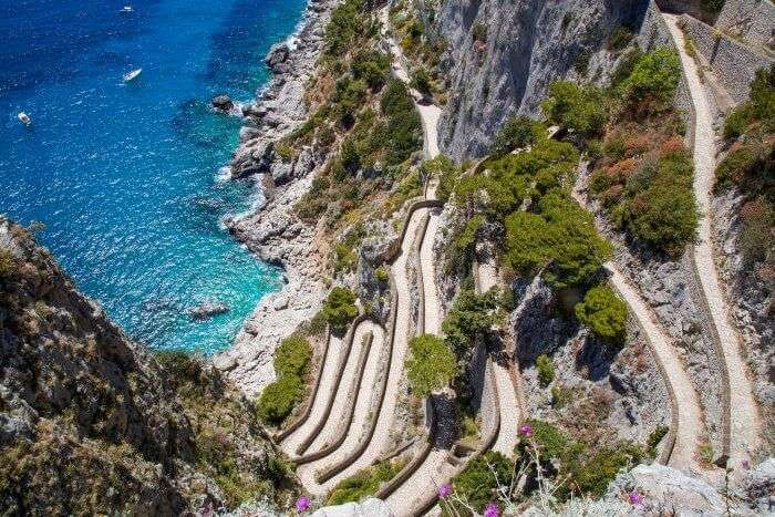 The snake like roads of Italy on the side of a cliff
