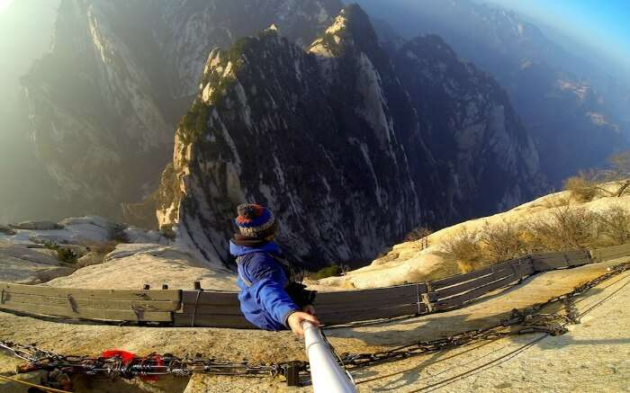 A person with selfie stick doing cliff walking in Huashan Mountain - one of the most extreme adventure activities
