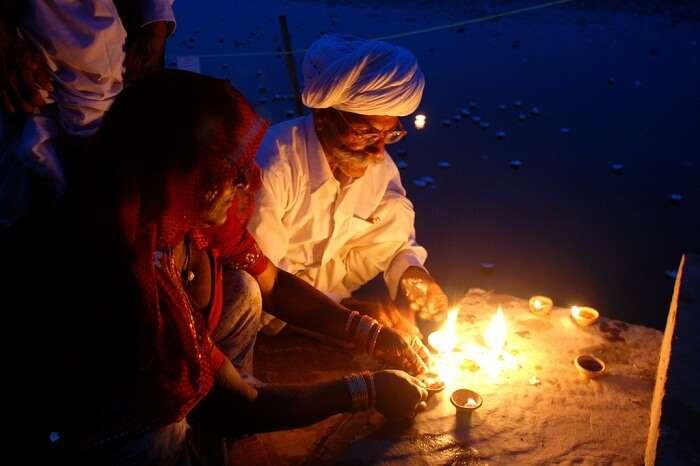 An elderly couple lights the diyas during the Kolayat Fair