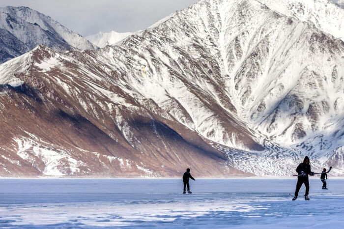 People playing ice hockey on frozen Pangong Tso