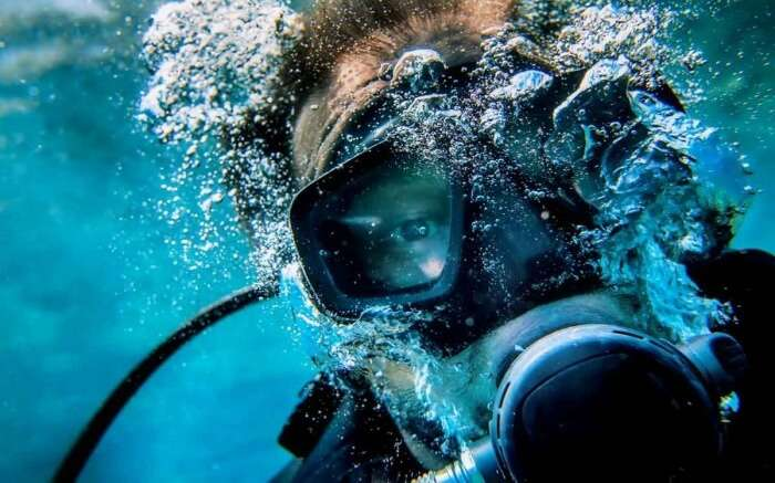 A scuba diver blowing bubbles under the sea