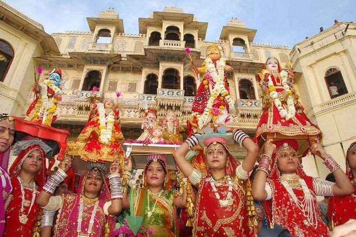 Devotees carrying idols of the gods and goddesses during the Mewar festival