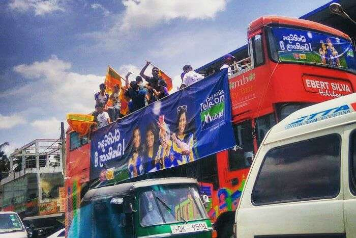 sri lankan cricket fans cheering for their team atop a bus