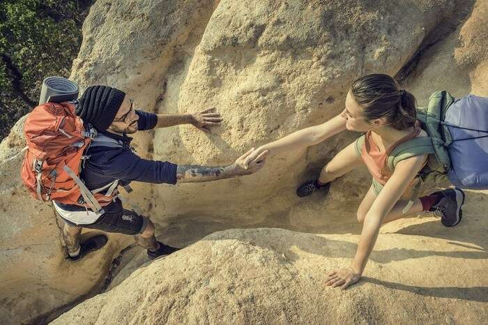 Travelers helping out each other while rock climbing