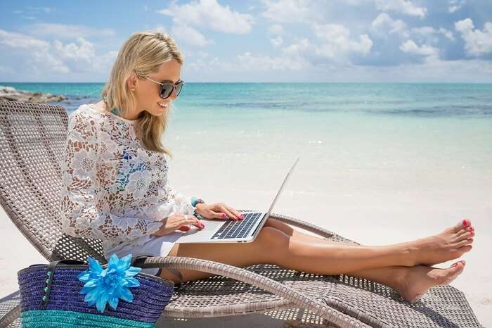 Woman working on her laptop on a beach