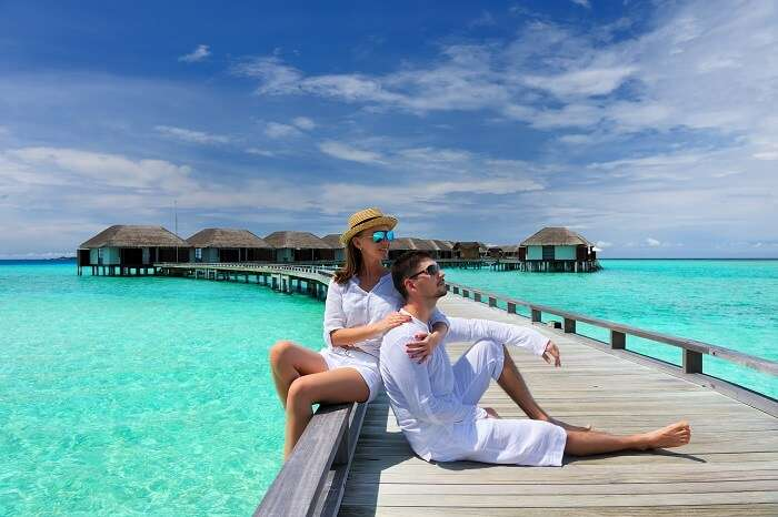 Couple on a tropical beach jetty at Maldives with the over water villas in the backdrop