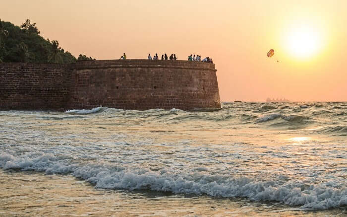 People looking at the sea while enjoying sunset from Aguada Fort in Goa which is one of the most popular forts of India