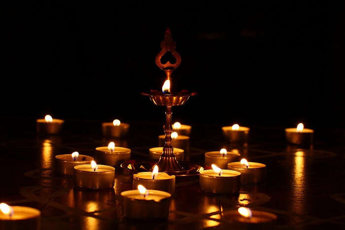 An array of diyas and a lamp lighted on the occasion of Karthigai Deepam