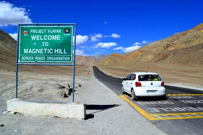 Signboard and mark on road mentioning the area under the influence of Magnetic Hill