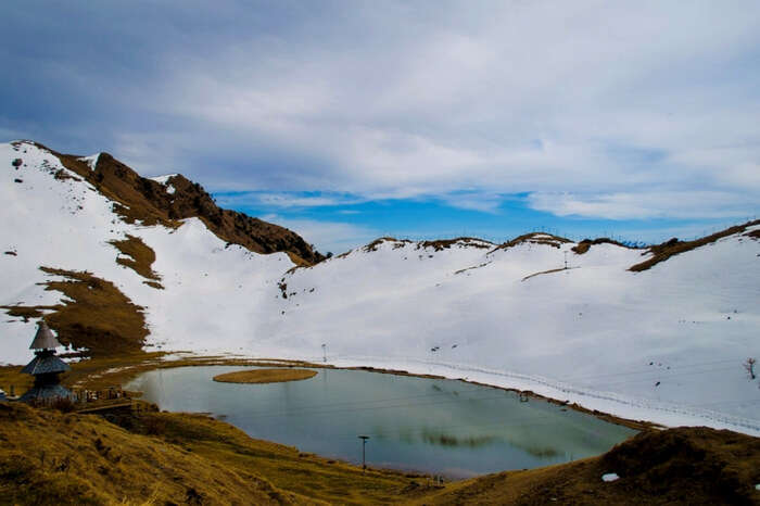 Picturesque view of Prashar Lake partially covered in snow