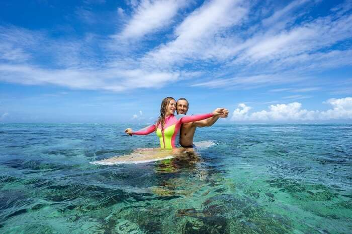 Young couple sitting on a surfboard in the open ocean in Mauritius