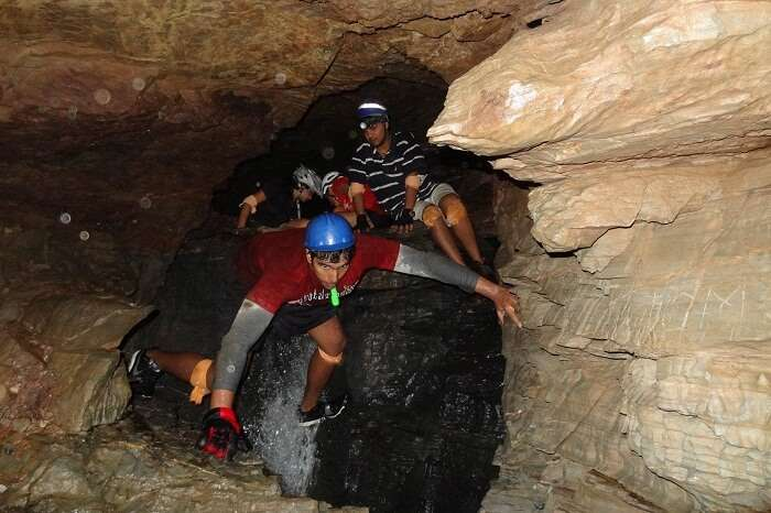 Tourists take a walk through the Budher Caves in Chakrata