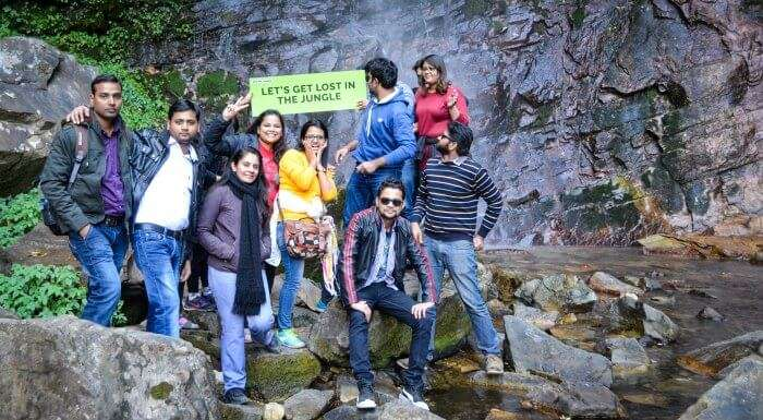 the whole group posing before the waterfall