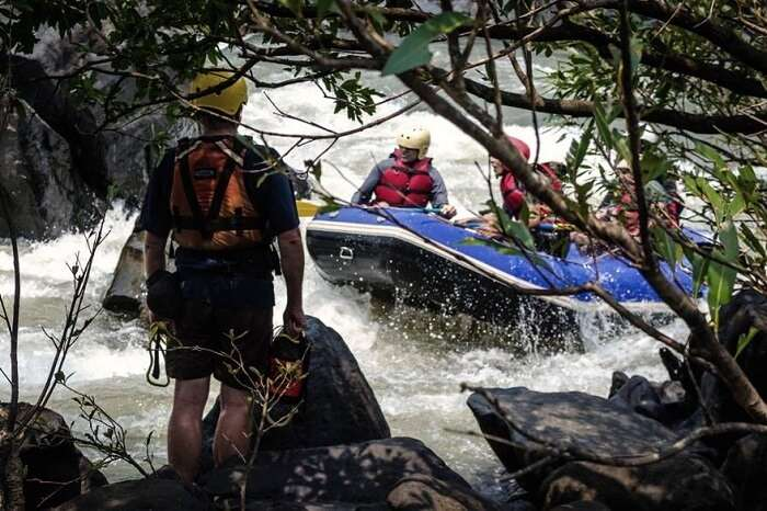 A tourist gets ready as others enjoy the thrilling sport of rafting in goa