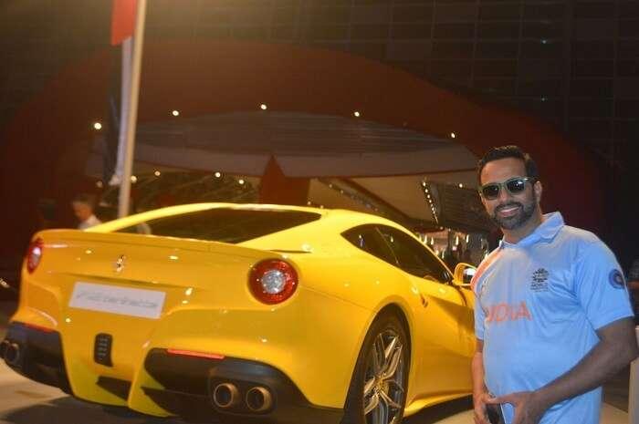 man posing next to a yellow ferrari