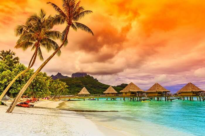 The Otemanu Mountain and the overwater villas in the backdrop of a beach at Bora Bora in French Polynesia