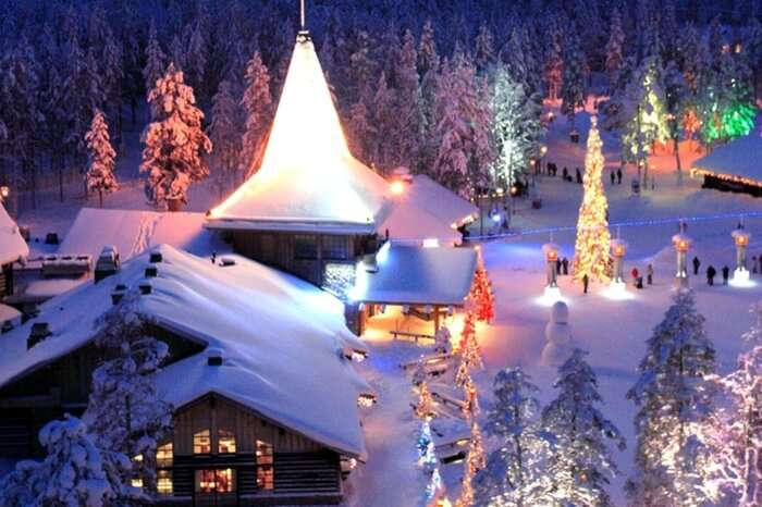 A well lit village in Lapland covered in snow during Christmas