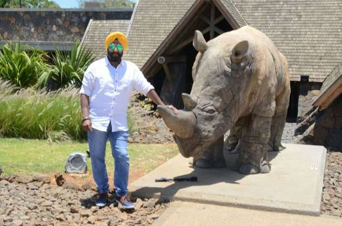 man posing next to rhino carved structure