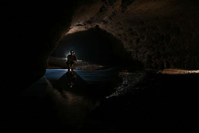 A cave explorer poses for a photograph at night at the Krem Liat Prah cave in India