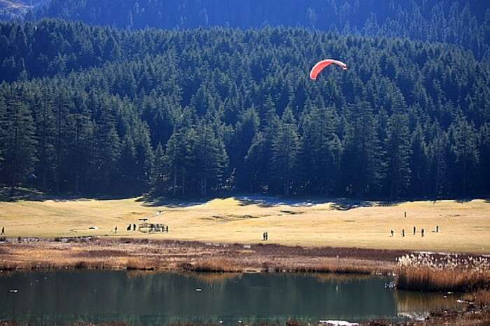 A paraglider landing at the base area in Khajjiar