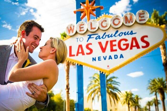 A couple poses at the welcome gate of Las Vegas