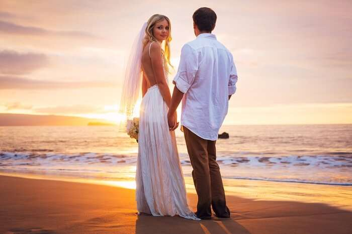 A sunset shot of a couple on a beach after renewing the wedding vows in Hawaii