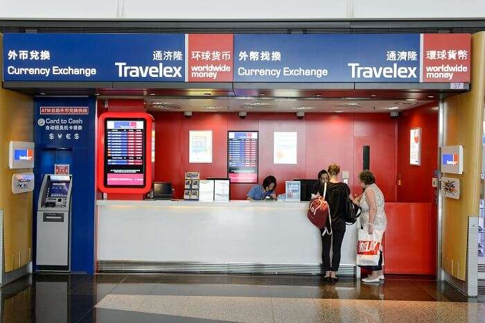 Travlers exchanging currency at the forex counter of Travelex at an international airport
