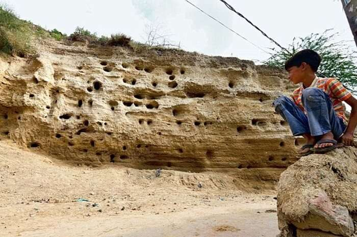 A child sits outside the ancient ruins of Rakhigarhi in India