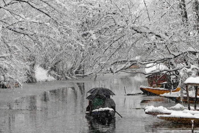Boat covered in snow sailing in the Dal Lake