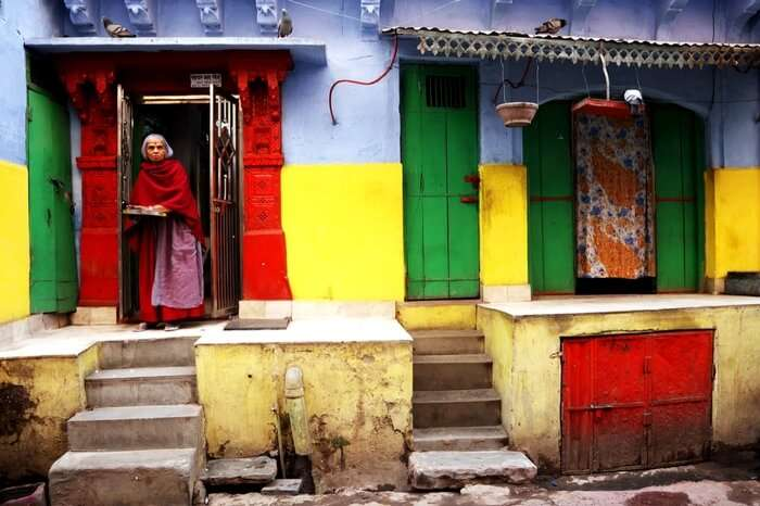 An old woman standing at the door of her colorful home