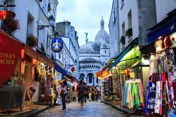 Tourists and Parisians walking around the shopping street of Montmartre in Paris