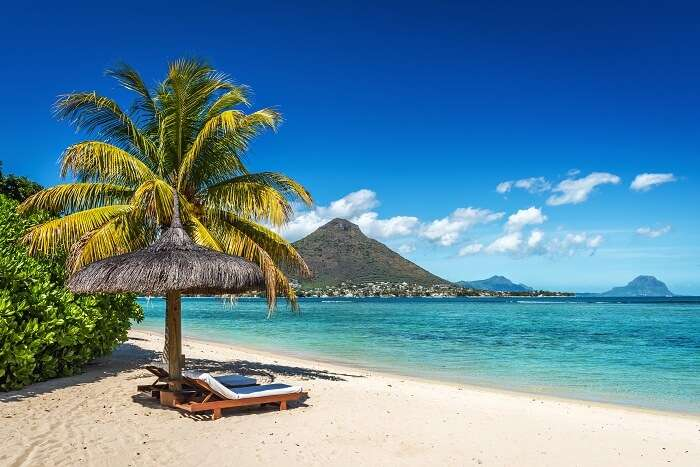Loungers and umbrella on tropical beach in Mauritius Island