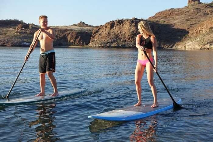 Couple enjoying stand-up paddle boarding on honeymoon