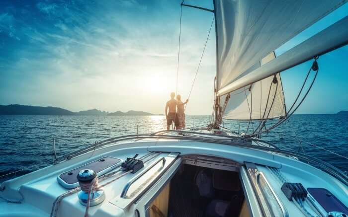 A couple facing sun onboard a yacht