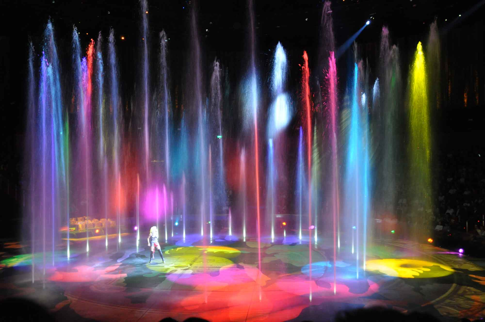 A lady performing solo in the middle of colorful water fountains