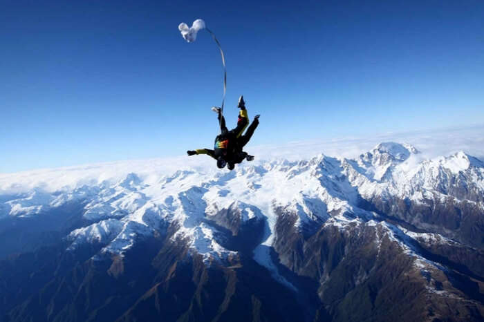 Skydivers during a freefall in the Fox Glacier region
