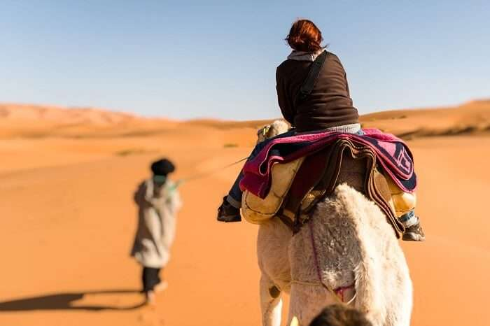 Woman traveling on camel led by a berber nomad
