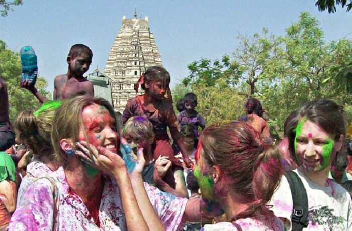 Foreign tourists enjoying applying colors at each other during holi celebrations at Hampi