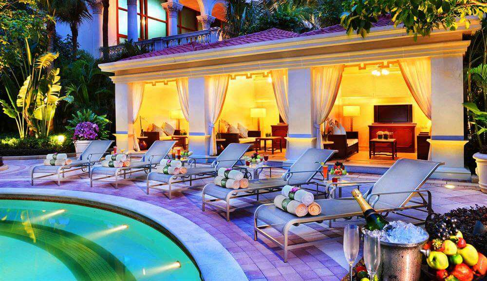towels rolled on sunbath lounges beside outdoor pool